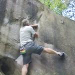 Climber on hard boulder problem.