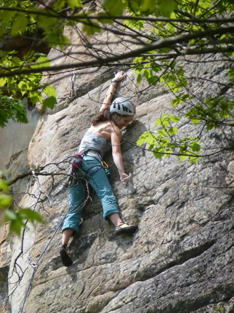 Climber making reachy moves on an outdoor route.