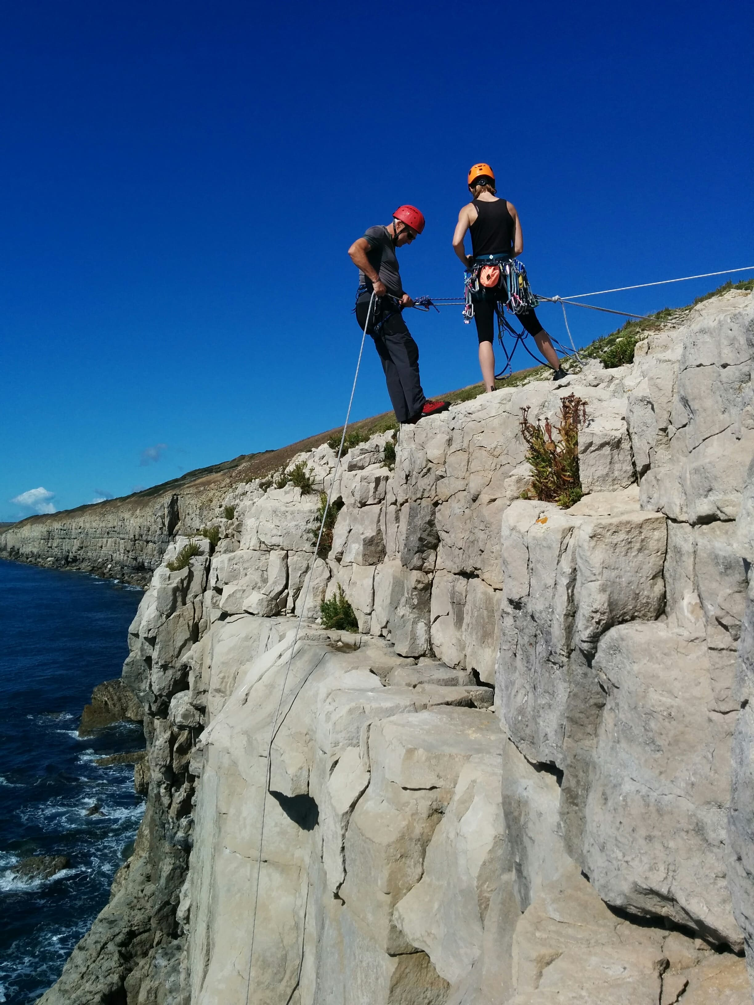 Sarah Laidler instructing a client in the art of safe abseiling at Swanage, Dorset.