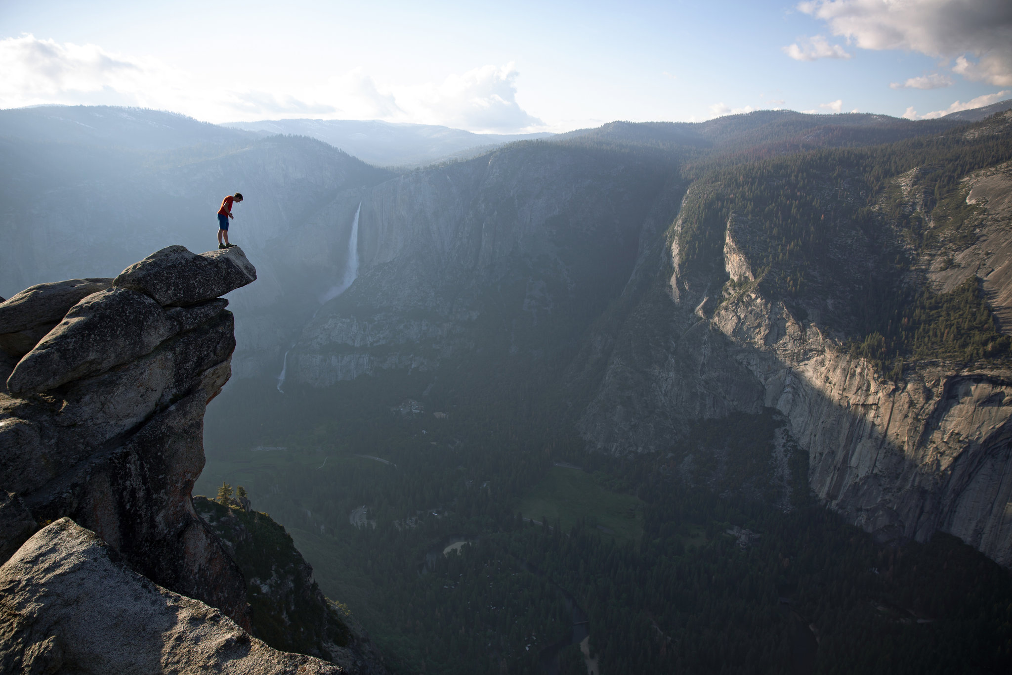 "Alex Honnold peering over the edge of Glacier Point in Yosemite National Park. He had just climbed 2,000 feet from the valley floor, as shown in the film ""Free Solo."" Credit Jimmy Chin/National Geographic"