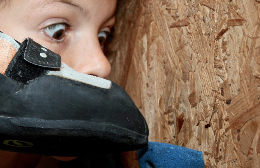 Climbing Footwork Basics image of a girl intensely looking at a rock shoe being placed correctly on a foothold!